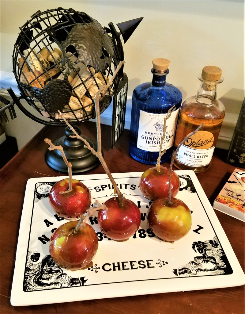 homemade caramel apples with natural twig skewers on a ouija board cheese platter