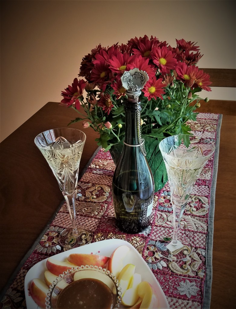 romantic glasses with prosecco, sliced apples, and homemade caramel sauce for dipping
