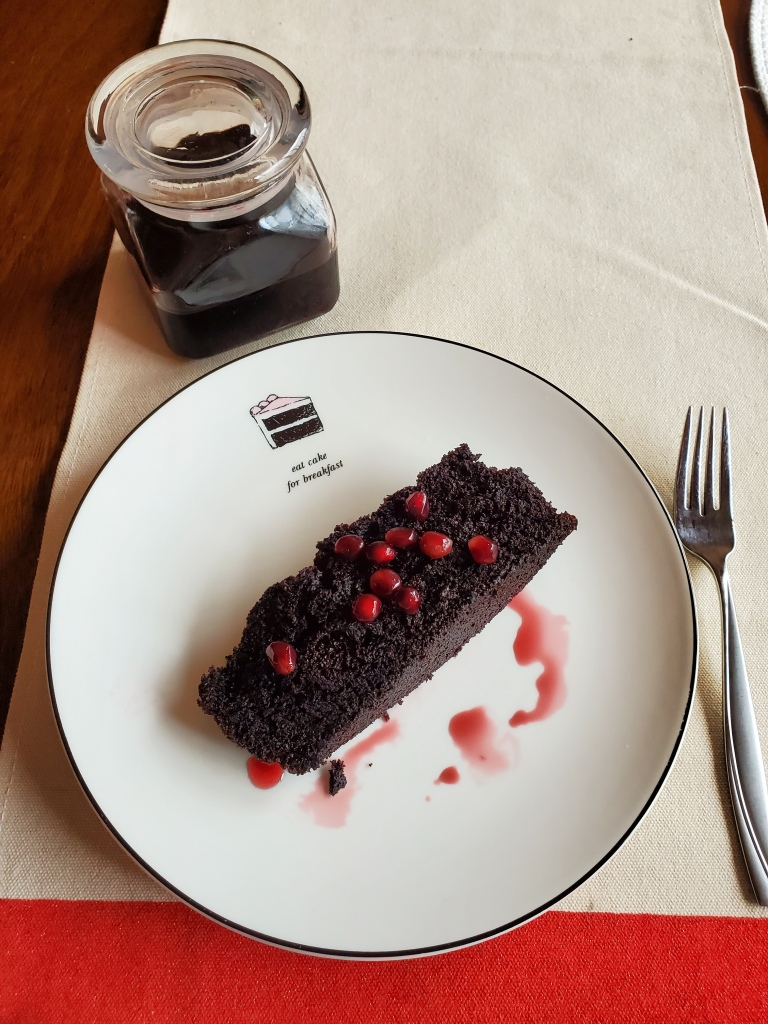 Slice of chocolate pomegranate cake with pomegranate molasses syrup in a jar