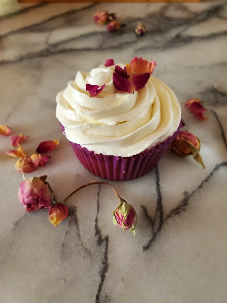 pistachio cupcake with rosewater buttercream and decorated with edible rose petals