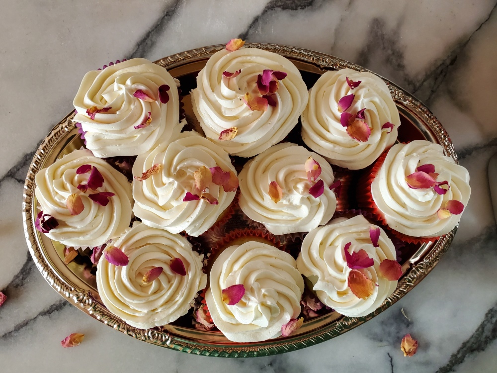 pistachio halva cupcakes with rosewater swiss meringue buttercream frosting and decorated with edible rose petals
